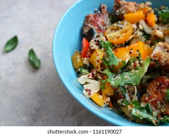 Freshly made quinoa salad with turkey fillet, salad mix, colorful cherry tomatoes and seeds. Healthy salad in a bowl on a grey stone background. Top view, space for text.