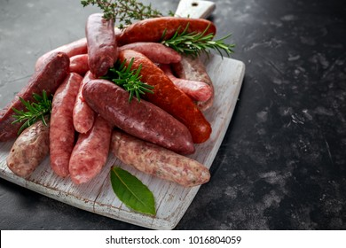 Freshly made raw breed butchers sausages mix in skins with herbs on white cutting board.