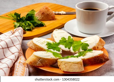 Freshly made sandwiches with cream cheese and parsley on a plate, chopping wooden board and a cup of coffee - morning and breakfast concept