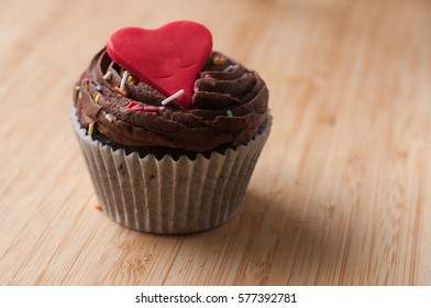 freshly made valentines cup cake lit by window light on wooden board