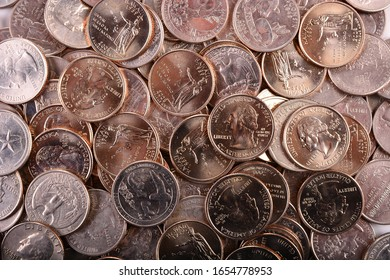 Freshly minted brilliant uncirculated and some circulated Washington quarters of various types and designs arranged as they lay for a numismatic background of USA coins. Reflective nickel surfaces.