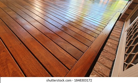 Freshly oiled Australian spotted Gum timber outdoor covered deck with Merbau stain at Residential Home, still wet and yet to dry - Shutterstock ID 1848303172