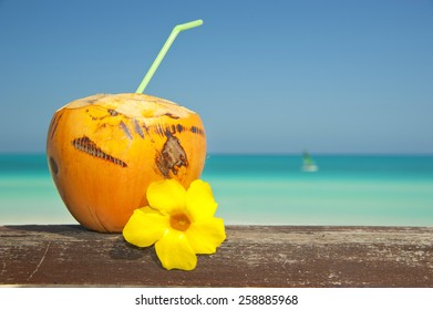 Freshly opened coconut with a straw and Atlantic Ocean in the background