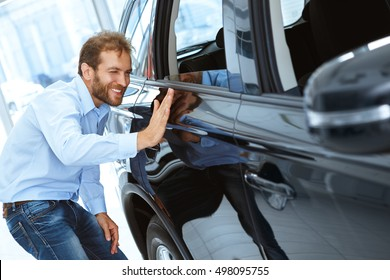 Freshly painted beauty. Shot of a handsome mature man choosing a car at the dealership touching a vehicle smiling cheerfully copyspace