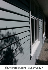 Freshly painted exterior weatherboard wall; cottage, path, midday shadows