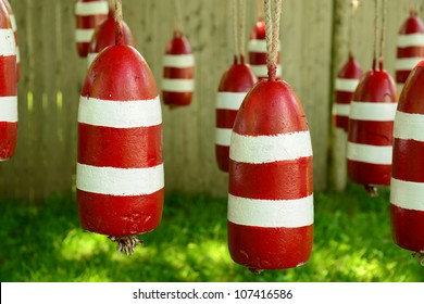 Freshly Painted red and white lobster fishing buoys hanging on a clothes line drying