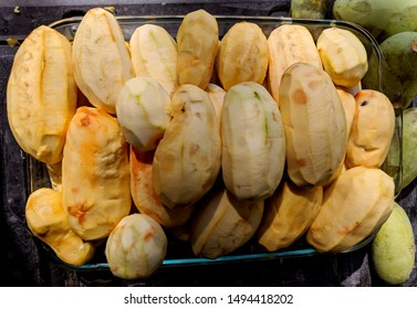 Freshly peeled creamy orange pawpaw fruits stacked in a glass dish on a black surface next to freshly picked green pawpaw fruit