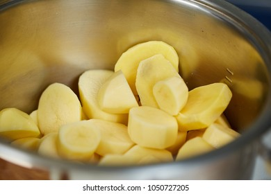 Freshly peeled and sliced new potatoes in a stainless steel pot