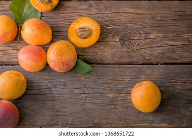 Freshly picked apricots, scattered on rustic wooden table.