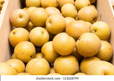 Freshly picked asian pears displayed in wooden crate