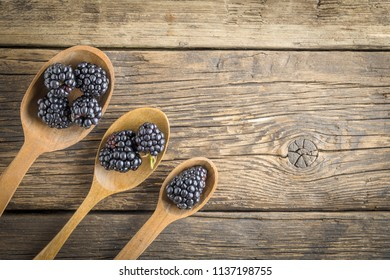 Freshly picked blackberries in the range of wooden spoons. Juicy and fresh blackberries on rustic table. Blackberry on wooden background.  Concept of healthy eating and nutrition for all family.