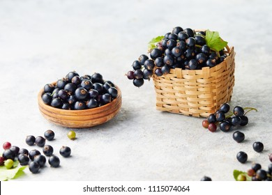 Freshly picked blackcurrants. Blackcurrants in a bowl and beside a small wicker basket of fresh blackcurrants.