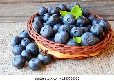 Freshly picked blueberries in a basket on a burlap cloth background.Fresh organic blueberry.Bilberries.Healthy eating,vegan diet or raw food concept.Selective focus.