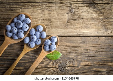 Freshly picked blueberries in the range of wooden spoons. Juicy and fresh blueberries on rustic table. Blueberry on wooden background.  Concept of healthy eating and nutrition for all family.