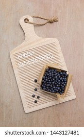 """Freshly picked blueberries in small produce basket on letterboard.  Letterboard says """"fresh blueberries.""""  Letterboard shaped like a cutting board."""