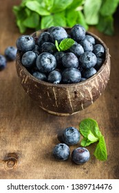Freshly picked blueberries in wooden bowl. Juicy and fresh blueberries with mint on wooden table. Bilberry on rustic background. Blueberry antioxidant. Concept for healthy eating and nutrition.