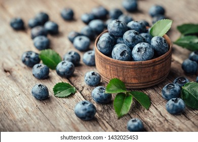 Freshly picked blueberries in wooden bowl on wooden background. Healthy eating and nutrition.