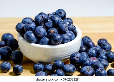 Freshly picked blueberries in wooden bowl. Juicy and fresh blueberries on wooden Background Selective Focus