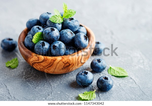 Freshly picked blueberries in wooden bowl. Juicy and fresh blueberries with green leaves on light gray background.