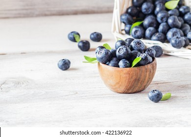 Freshly picked blueberries in wooden bowl.fresh blueberries with  leaves on a white rustic table. selective focus.