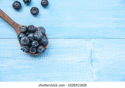 Freshly picked blueberries in wooden spoon on blue background. Ripe and juicy fresh.