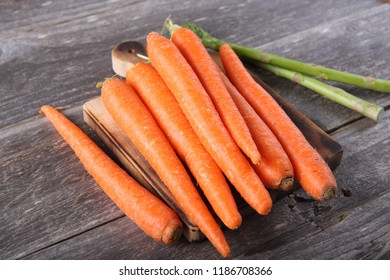 Freshly picked carrots and asparagus on wood background
