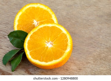Freshly picked and cut oranges with leaves on a wooden background