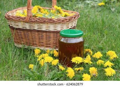 freshly picked dandelion flowers in a wicker basket and dandelion honey in a glass on the lawn