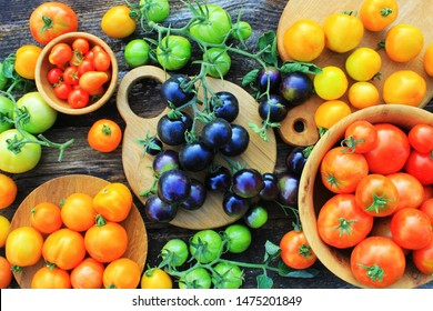 Freshly picked heirloom tomato harvest: pear shaped, beef heart, tigerella, brandywine, cherry, black, indigo rose, green. Organic produce at a Farmer's market.