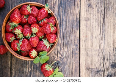 Freshly picked juicy organic strawberries with leaves in ceramic bowl on rustic aged wooden table surface with copy space.