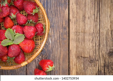 Freshly picked juicy organic strawberries with leaves in wicked bowl on rustic aged wooden table surface with copy space.