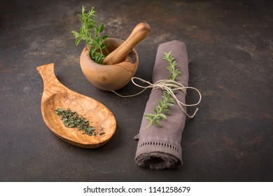 Freshly Picked Oregano in Wooden Mortar and Pestle; Chopped Oregano in Wooden Spoon; Sprig of Oregano in Napkin; Black Background
