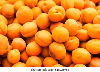 freshly picked organic apricots on display at the farmers market, background texture