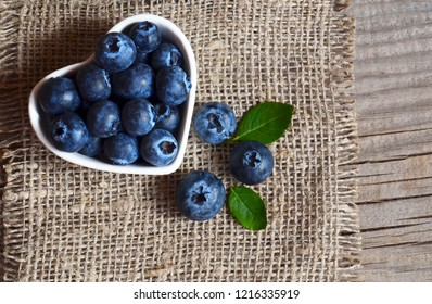 Freshly picked organic blueberries in a heart shaped bowl on a burlap cloth background.Blueberry. Bilberries. Healthy eating,vegan food or diet concept.