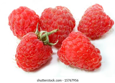 Freshly picked raspberries against a white background.