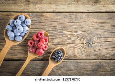 Freshly picked raspberries, blueberries and blackberries in the range of wooden spoons. Juicy and fresh berries on rustic table. Concept of healthy eating and nutrition for all family.
