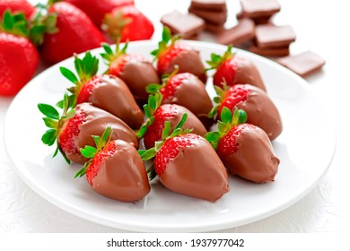 Freshly picked strawberries covered in chocolate. Exquisite dessert. Isolated on white background. French cuisine.