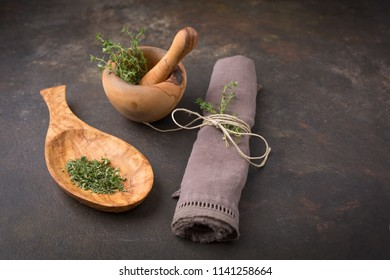 Freshly Picked Thyme in Wooden Mortar and Pestle; Chopped Thyme in Wooden Spoon; Sprig of Thyme in Napkin; Black Background