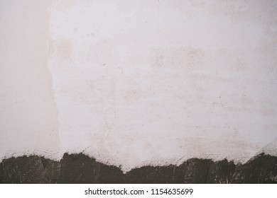 freshly plastered interior wall with mortar on the bottom