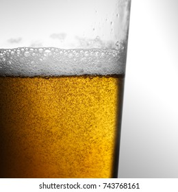 Freshly poured amber gold beer with frothy head and bubbles in a glass