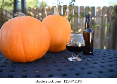 Freshly poured home brewed pumpkin ale beer with pumpkins and bottle in background