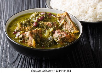Freshly prepared Ghormeh Sabzi of lamb stew meat with herbs and beans close-up in a bowl and rice on the table. horizontal