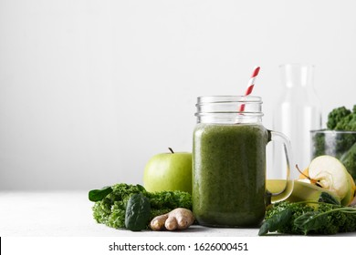 Freshly prepared jar of green smoothie, close up. Fresh vegetable smoothie on a light background. Vegetable smoothie with spinach and kale cabbage.
