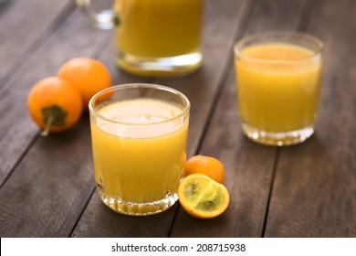 Freshly prepared juice out of Naranjilla or Lulo fruits (lat. Solanum quitoense) with fruits on the side and in the back (Selective Focus, Focus on the front rim of the glass)