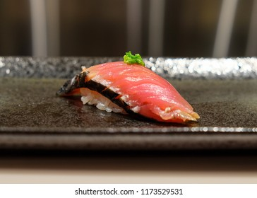 Freshly prepared raw hay smoked bonito sushi on a plate.