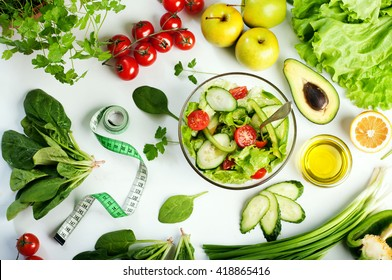 Freshly prepared salad vegetables. Concept diet food. White background. The variety of vegetables and herbs next to the plate with a salad.