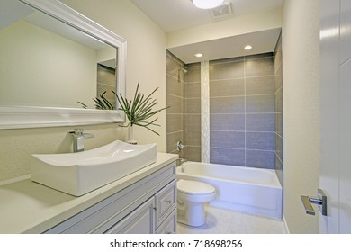 Freshly renovated bathroom features shower tub combo with grey subway tile, a white nailhead mirror mounted over a sink vanity with a polished nickel modern faucet.