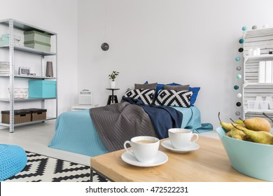 Freshly renovated bedroom arranged in white and blue, with a wooden coffee table with coffee cups in the foreground
