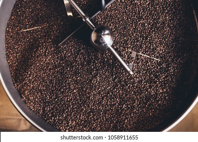 Freshly roasted aromatic coffee beans in a modern coffee roasting machine.