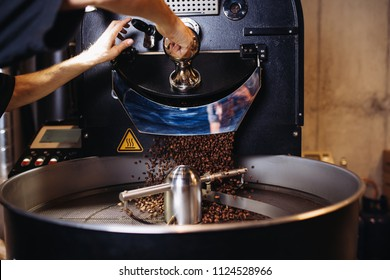 Freshly roasted coffee beans pouring from a large coffee roaster into the cooling cylinder.